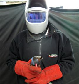 Welder in welding mask and protective clothing